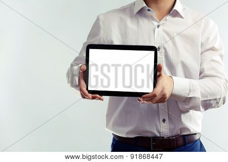 Man holding tablet on grey background
