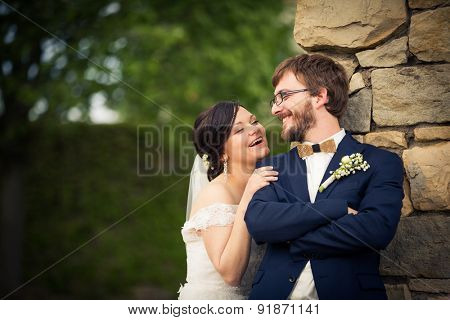 Portrait of a young wedding couple on their wedding day, looking happy, laughing together instead of posing properly for the photographer