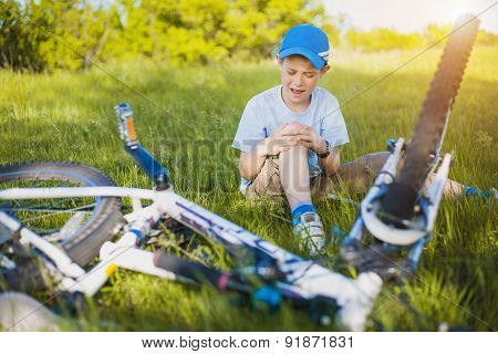 Crying boy with a bleeding injury near bike that he has fallen from