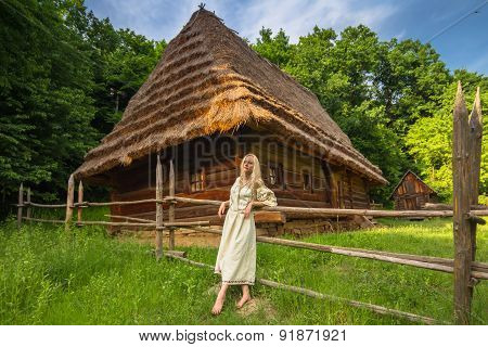 Young Woman In Ukrainian National Costume Near Old House