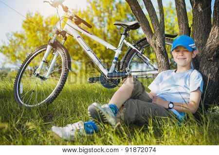 happy kid with a bicycle resting under a tree