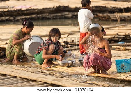 MANDALAY,MYANMAR,JANUARY 19, 2015: Women taking shower and washing dishes in a slum area at the Irrawaddy river in Mandalay, Myanmar (Burma).