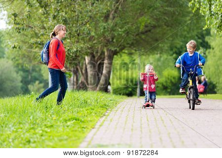 happy mother with two kids on scooter and bike in the park