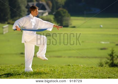Tai Chi Exercise With Sword In Nature On Green Field
