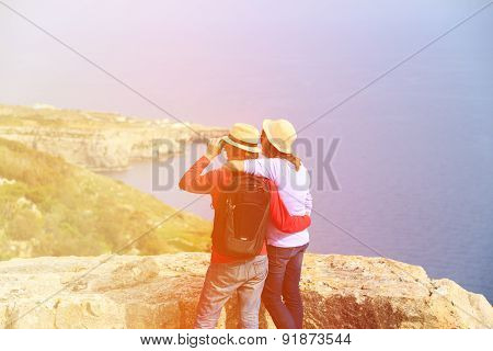 young couple hiking in mountains looking at binocular