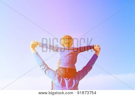 father and little son on shoulders play at sky