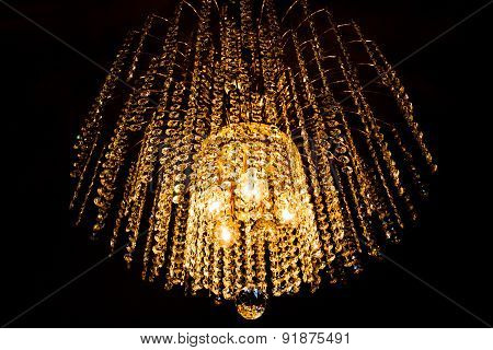 A Crystal Chandelier Glows With Golden Light