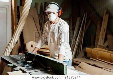 Carpenter using protective wear and working on wood machine