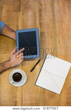 Man working on tablet on wooden table