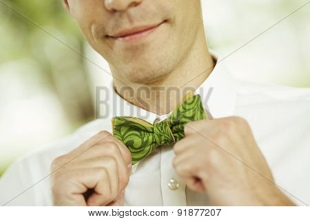Close Up Handsome Businessman Fixes His Bow Tie And Smile