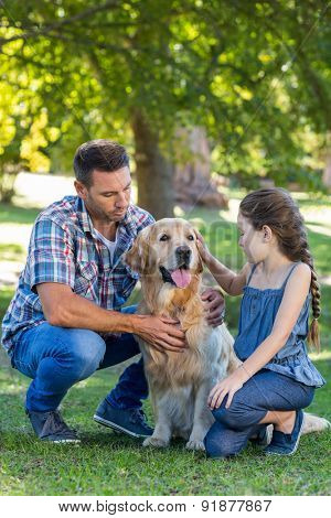 Father and daughter with their pet dog in the park on a sunny day