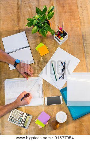 Man writing on clipboard on working desk
