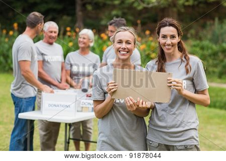 Happy volunteer family holding donation boxes on a sunny day