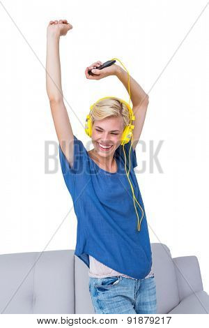 Happy blonde woman listening music with her mobile phone on white background