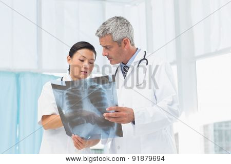 Male and female doctors examining x-ray in the medical office
