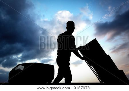 Delivery man pushing trolley of boxes against cloudy sky