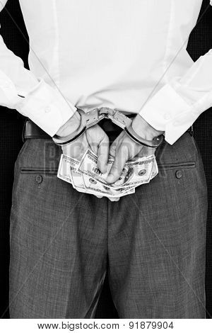 Businessman in handcuffs holding bribe against black background