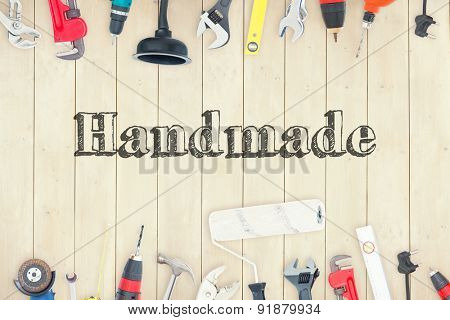 The word handmade against diy tools on wooden background