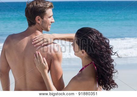 Pretty brunette putting sun tan lotion on her boyfriend at the beach