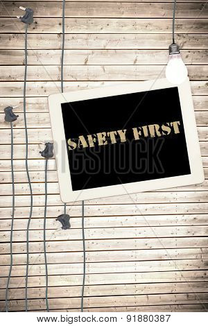 The word safety first against tablet and plugs on wooden background