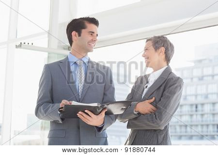Business colleagues smiling at each other in the office