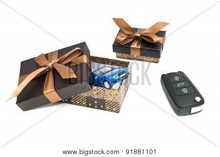 Blue Car, Keys And Brown Gift Boxes On White