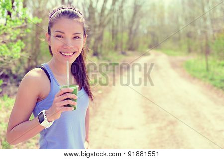 Healthy fitness girl drinking green spinach vegetable smoothie wearing smartwatch heart rate monitor during outdoor running workout in forest park during summer or spring. Happy fit Asian woman.