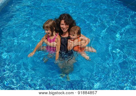 Happy family having fun in swimming pool on summer vacation, mother and kids