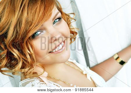 Stylish smiling young woman with curly short red hair.