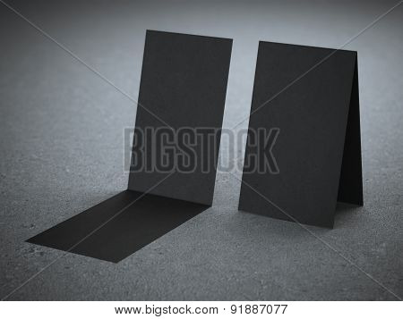 Two folded black business cards