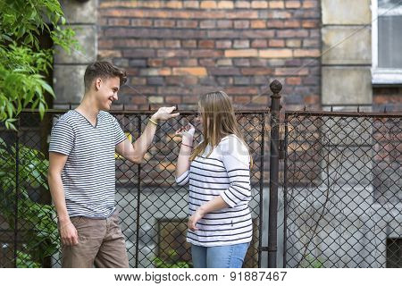 Teenagers, boy and girl talking on the street.