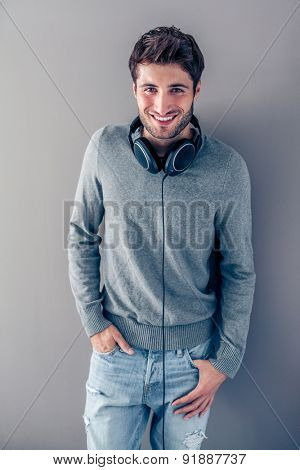 Handsome young smiling man listening to music in front of a grey wall