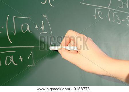 Teacher hand writing formulas on blackboard background