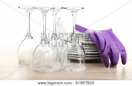 Dishes in foam with gloves on table isolated on white
