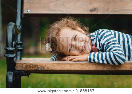 Portrait Of Little Girl Lying On Bench In A Park, Leisure In The Nature. Close-up
