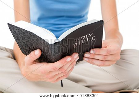 Woman sitting on the floor and reading bible on white background