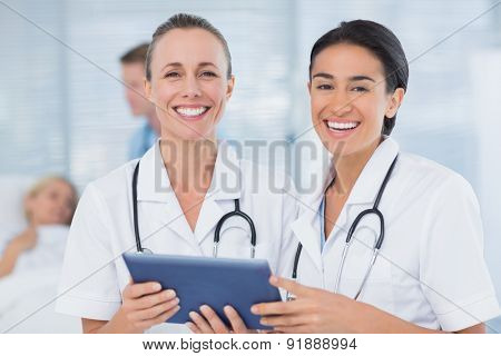 Happy doctors looking at clipboard while theirs colleagues speaks with patient in the hospital