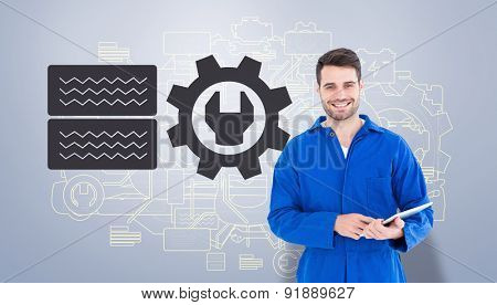 Happy young male mechanic using digital tablet against grey vignette