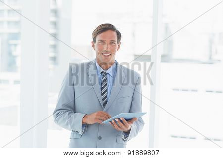 happy businessman using tablet pc in office