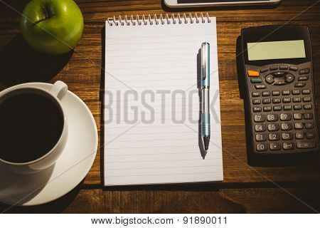 Overhead shot of notepad and calculator on a students desk