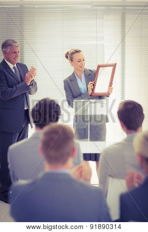 Pretty businesswoman receiving prize in meeting room