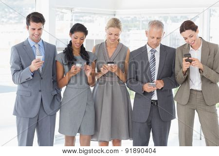Employees using their mobile phone in the office