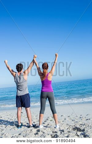 Happy couple raising their hands at the beach