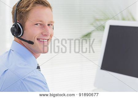 Handsome agent with headset typing on keyboard in call center