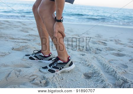 Fit man having muscle pain at the beach