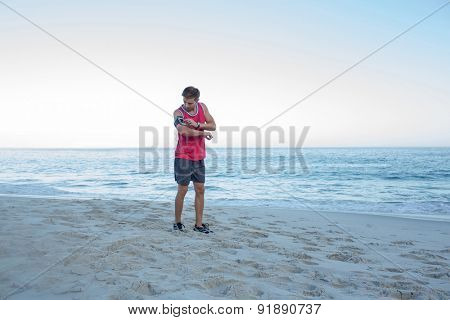 Handsome fit man ready to run at the beach