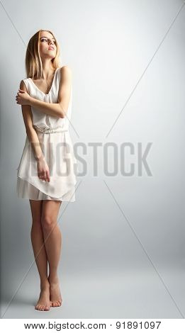 Expressive young model in white dress on gray background