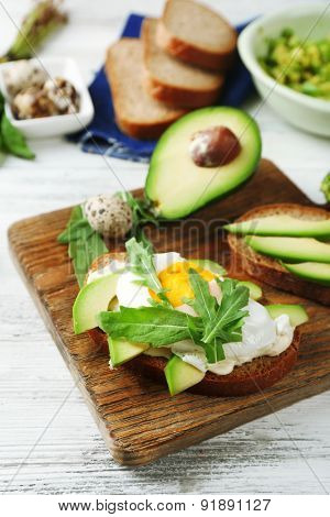 Tasty sandwiches with egg, avocado and vegetables on wooden background