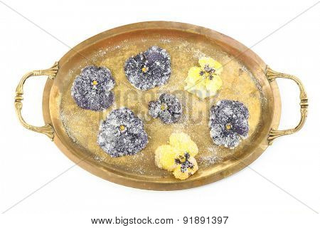 Candied sugared violet flowers on tray, isolated on white
