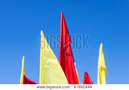 Red And Yellow Flags Fluttering In The Wind Against Blue Sky